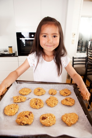 messy kitchen: Cute young girl looking at camera with bakng sheet full of raw cookies