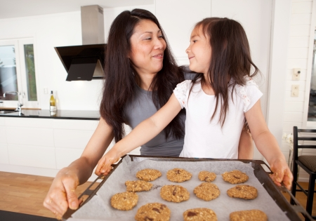 baking tray: Mother and daughter baking cookies together, holding tray of raw cookie dough Stock Photo