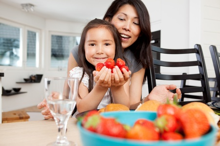 Mother and daughter sitting at table in kitchen with handful of strawberries photo