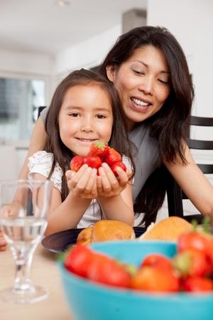 tentempi�: Sonriendo madre e hija con fresas frescas cosechadas Foto de archivo