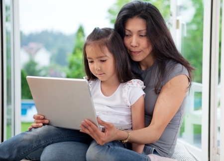 Cute young daughter together with mother using a laptop in a house interior photo