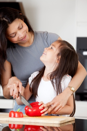 asian cook: Mother and daughter cutting vegetables together