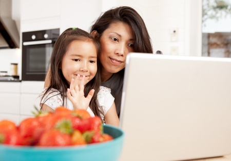 chat online: Mother and daughter using computer, waving while in a live video chat Stock Photo