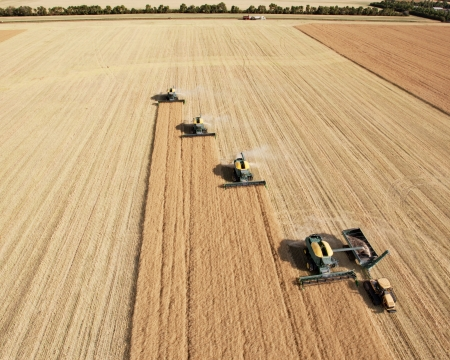 manitoba: Four harvesters combing on a prairie landscape in formation