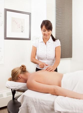 acupuncturist: Acupunturista mujeres profesionales que trabajan con una paciente en una cl�nica Foto de archivo