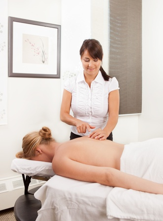 Professional female acupuncturist working with a female patient in a clinic photo