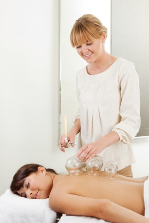 Happy professional accupunctureist removing fire cupping globes from patient Stock Photo - 10988878