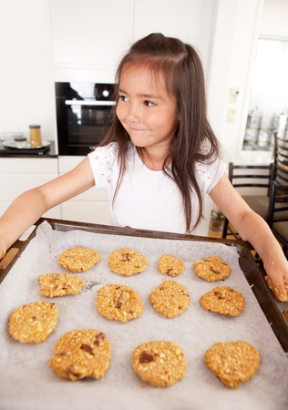 messy kitchen: Young girl with cookie sheet filled with raw cookies
