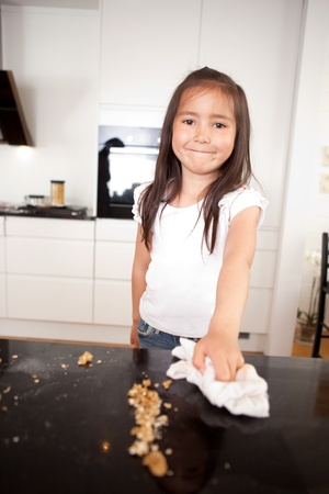 messy kitchen: Young smiling cute girl wiping the counter after making cookies