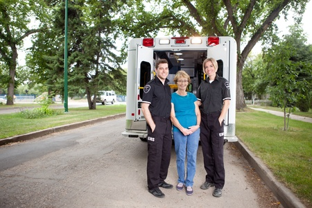 Happy patient in residential area of city standing with paramedics and ambulance photo