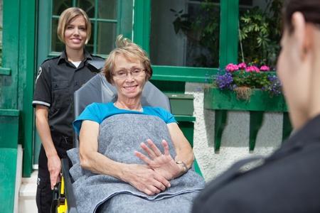 paciente en camilla: Paciente mayor en una camilla siendo empujado por los profesionales médicos de emergencia. Poca profundidad de enfoque DOF, en el paciente crítico