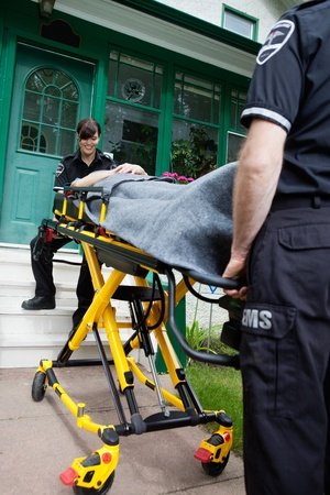 cfr: Ambulance worker smiling to patient outside house Stock Photo
