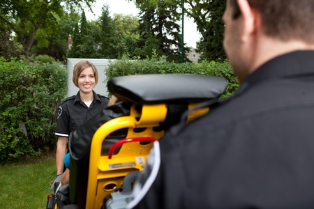 Female paramedic with a smile pulling a stretcher to the ambulance Stock Photo - 10989238