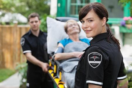 Ambulance Arbeiter Porträt mit Trage, paitient und Mitarbeiter Standard-Bild