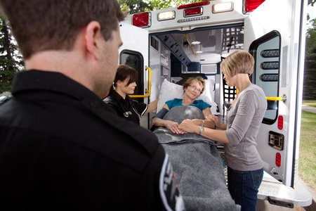 cfr: Senior woman being transported to hospital by paramedics, caregiver at side holding her hand Stock Photo