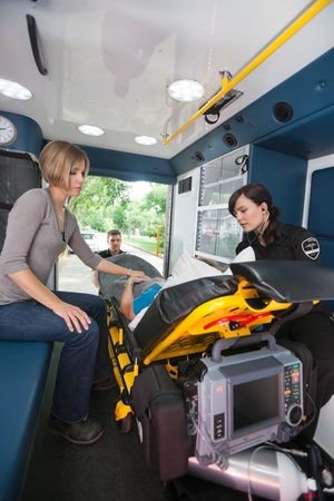 EMT professional caring for a senior woman in an ambulance, caregiver at side photo