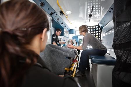 paciente en camilla: Interior de la ambulancia con la mujer mayor de ser transportados a un hospital, el médico de al lado