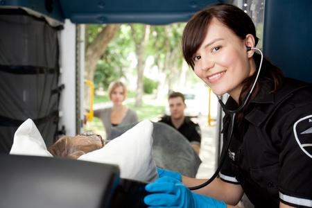 paciente en camilla: Retrato de un paramédico para escuchar la frecuencia cardíaca del paciente en ambulancia