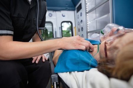 cfr: Detail of EMT worker listening to heart of senior woman patient in ambulance