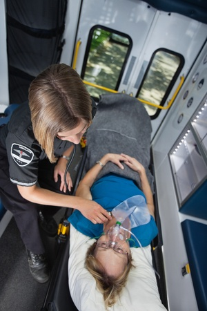 Senior woman in ambulance receiving emergency medical care photo