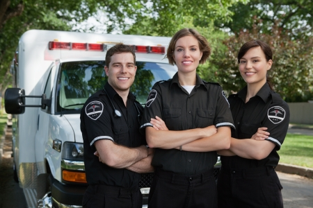 Group of three paramedics standing in front of ambulance with smile