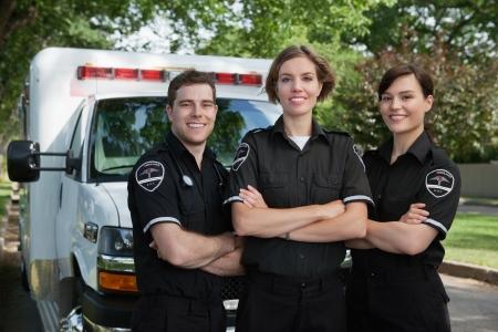 Gruppe von drei Sanitätern stand vor der Krankenwagen mit einem Lächeln