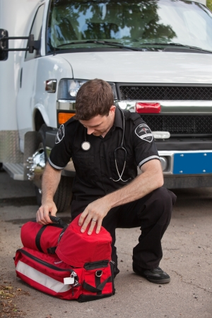 cfr: Male emergency medical services professional (EMS) with portable oxygen unit near ambulance Stock Photo