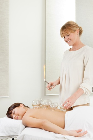 cupping therapy: Young relaxed woman receiving fire cupping from a professional acupuncture therapist Stock Photo