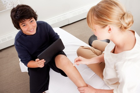 acupuncturist: Young male receiving pediatric acupuncture while playing games on a digital tablet Stock Photo