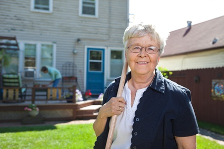 backyard woman: Portrait of senior woman holding gardening tool with friend in the background