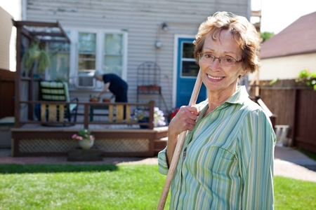 Portrait of elderly woman holding gardening tool with friend in the background Stock Photo - 11048315