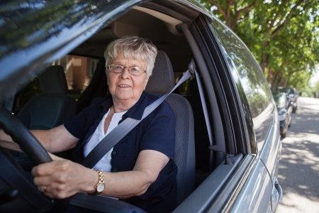 auto glass: Portrait of smiling old woman driving car