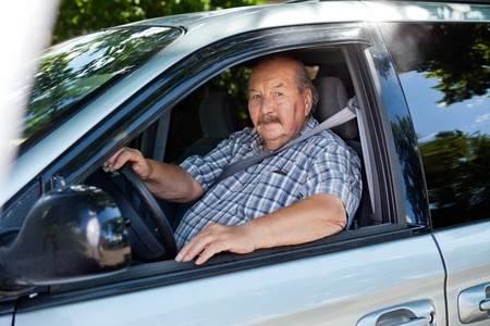 Portrait of an elderly man driving a car photo