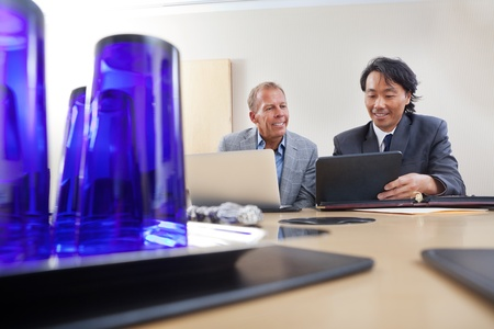 Two handsome businessmen working together on a laptop and digital tablet Stock Photo - 11048143