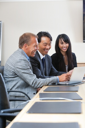 Smiling business people laughing while looking at laptop Stock Photo - 11048290