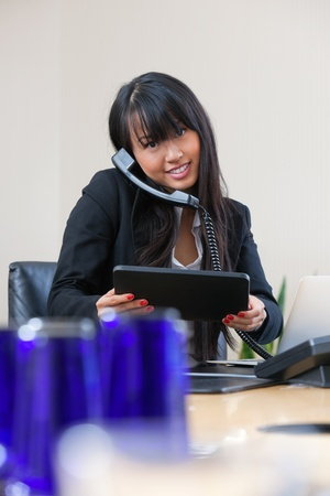 Portrait of smiling businesswoman having conversation on phone with digital tablet in hand photo