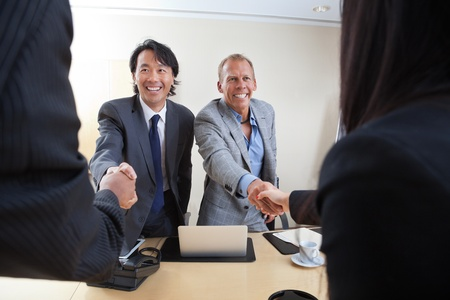 technology deal: Smiling business people shaking hands in office Stock Photo