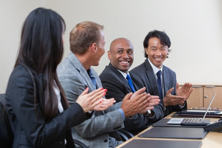 Business people applauding and smiling in presentation room photo