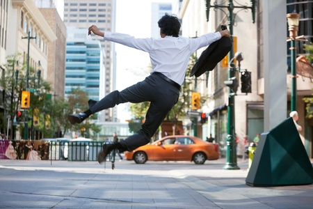 air jump: Rear view of business man jumping in air and kicking heals Stock Photo