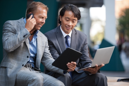 telephone together: Businessmen using laptop and tablet pc while communication on cell phone Stock Photo