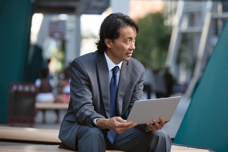 Businessman holding laptop and looking away Stock Photo - 11048271