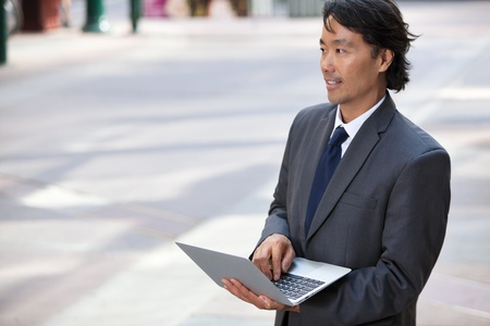 Handsome businessman using laptop outdoors photo