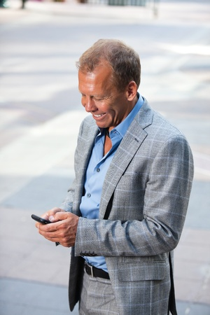 Portrait of happy businessman text messaging Stock Photo - 11048272
