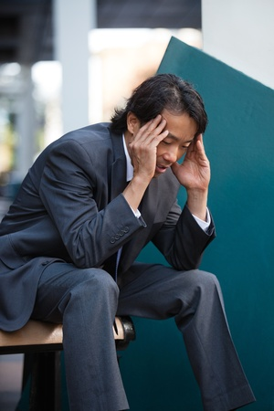 Business man sitting on bench outdoors not feeling well Stock Photo - 11048352