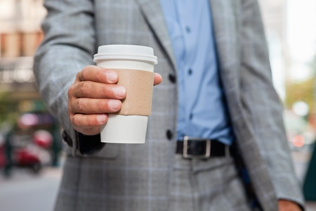 Mid section of businessman holding disposable coffee cup photo