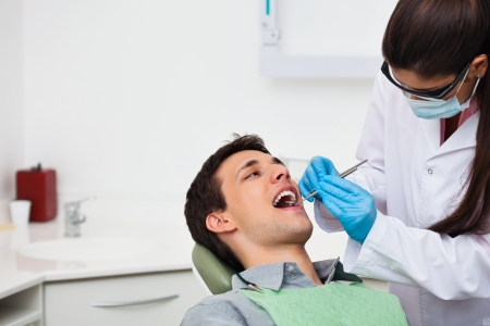 dentist mask: Female dentist examining a male patient at clinic Stock Photo
