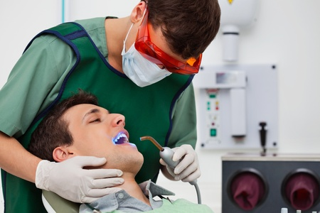 Dentist using UV light on patients teeth (dentist, patient,\ male)