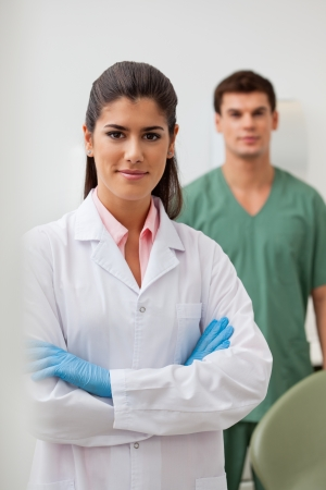 Portrait of confident female dentist with colleague standing in background Stock Photo - 11048264