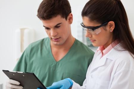 uniformes de oficina: Mujer dentista mostrando algo a su colega en el portapapeles