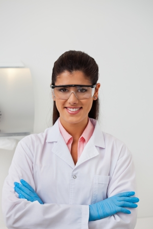 Portrait of attractive smiling female dentist with hands folded photo